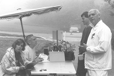 In 1996, the leadership team was able to conduct the first Members Plant Exchange from beneath a patio umbrella. At right, council member Roger Dietz, who suggested and chaired the event.